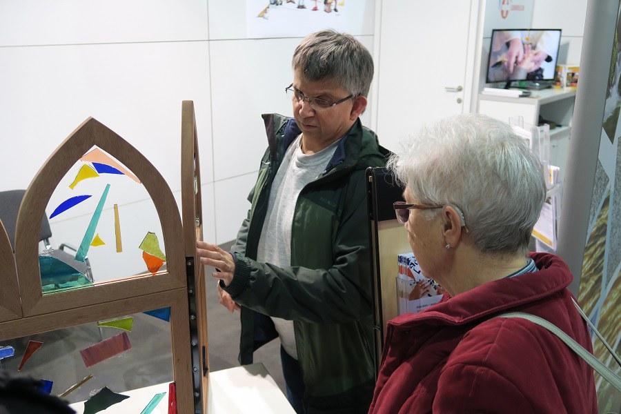 Besucher gestalten ein Kirchenfenster am Stand der Behindertenseelsorge