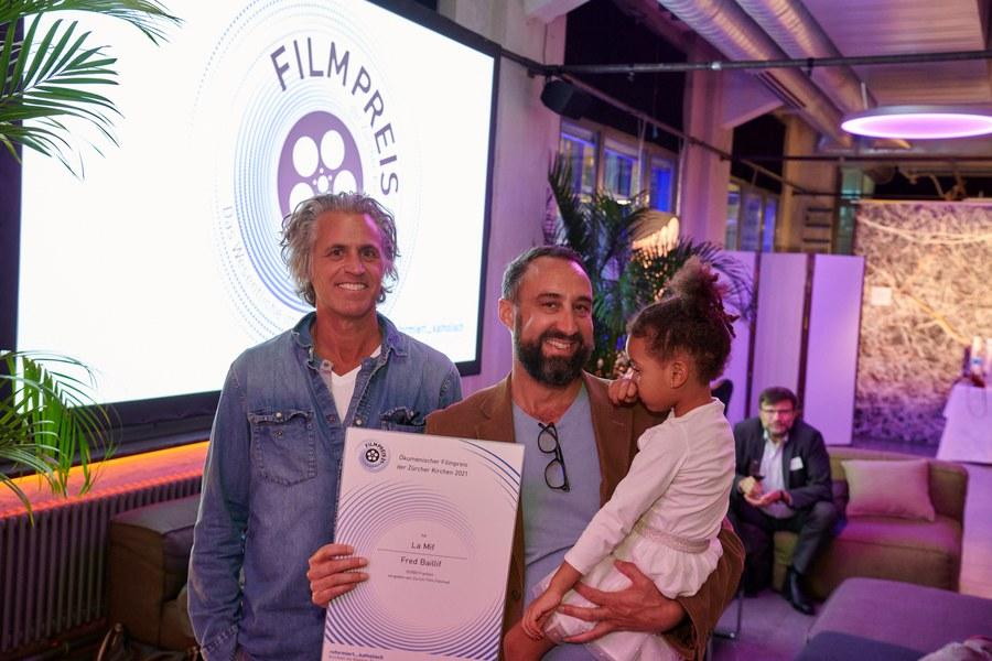 Kameramann Joseph Areddy (links) und Regisseur Fred Baillif mit Kind und Preis-Urkunde