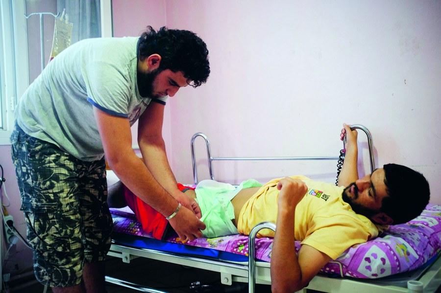 Spital Dar Alstshfaa, Türkei, Mai 2014: Die beiden Cousins Mohammed Azara (26) und Jeja Zougib (18)kämpften als Rebellen der FSA in Syrien. Im überlasteten Spital pflegt nun der ältere den verletzten jüngeren Kämpfer. Foto: Joseph Khakshouri