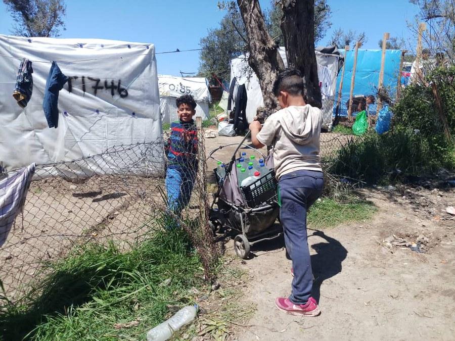 Kinder transportieren Wasser im Lager.