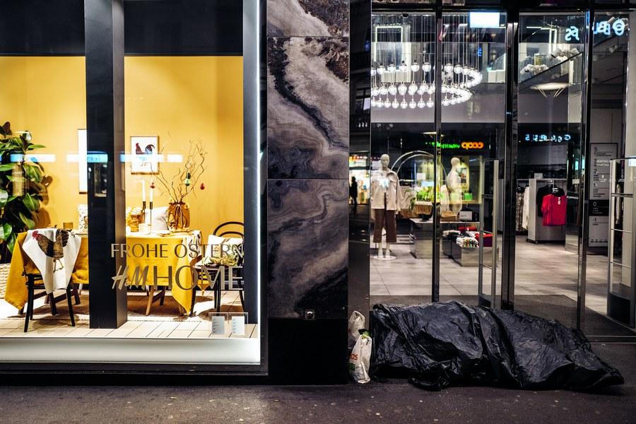 Die Pandemie verschärft die Kluft in der reichen Schweiz: Schutz- und wärmesuchend übernachtet ein randständiger Mensch an der Bahnhofstrasse in Zürich vor goldschimmernden Schaufenstern. Frohe Ostern!