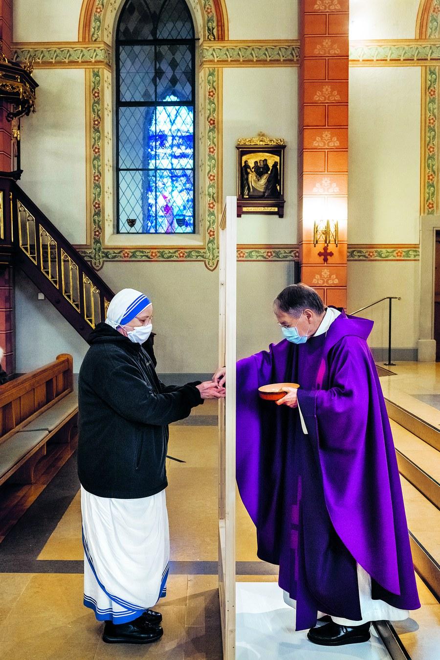 Brot-Teilen in ausserordentlichen Zeiten: Pfarrer René Berchtold reicht in der Stadtzürcher Kirche St. Peter und Paul einer Ordensschwester die Kommunion durch eine Plexiglastrennwand