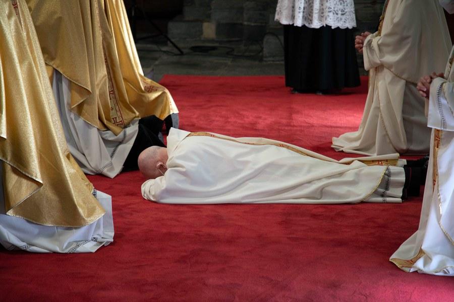 Joseph M. Bonnemain legt sich vor seiner Weihe vor dem Altarraum flach auf den Boden. Foto: Christoph Wider / forum